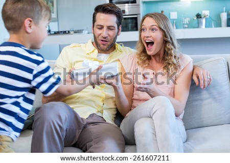 Son surprising his mother with gift at home in the living room - stock photo