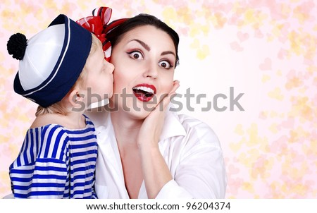 Son tender kissed his mother. pink background with hearts - stock photo
