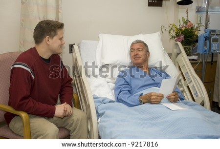 Son visiting his Dad in the hospital - stock photo