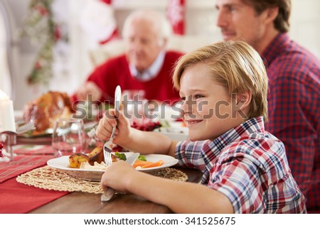 Son With Father And Grandparents Enjoying Christmas Meal - stock photo