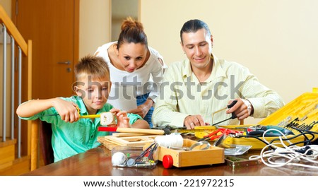 Son with father doing something with working tools, happy woman watching them at home - stock photo