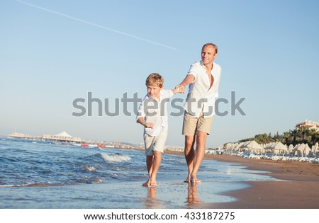 Son with father run together on the sea surf line
