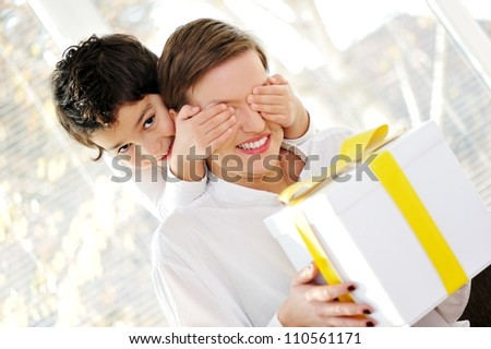 Son with surprise for mother - stock photo