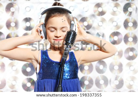 Song - musical child .Child, teen, girl, singing into a microphone, a small singer  - stock photo