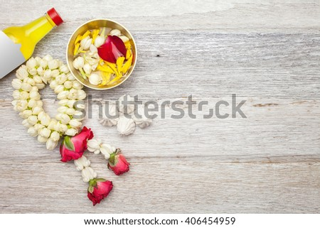 Songkran Festival : Perfume,Garland,floral and power on white wooden background - stock photo