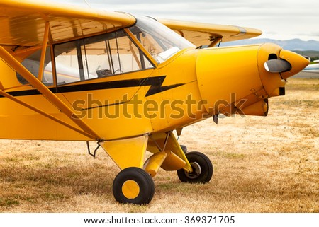 SONOMA, CA- May 27, 2013: Yellow Piper Cub airplane on a grassy field. An example of the vintage small American lightweight planes built between 1937 and 1947, still very popular today. - stock photo