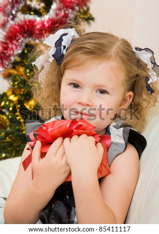Soon new year! Little girl at a Christmas fir-tree.