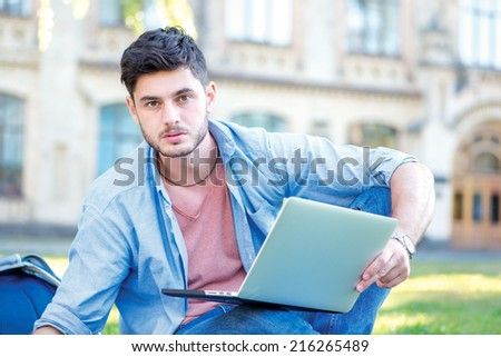 Soon to go to practice. Cute male student holding a laptop and reading a book and looking at the camera while sitting on the grass near the campus of the University at the break. - stock photo