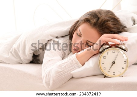 soon to wake up for sleeping attractive young woman with alarm clock - stock photo