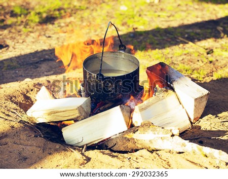 sooty cauldron on campfire at forest, sunny day - stock photo
