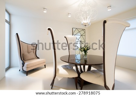 Sophisticated apartment with glass coffee table and fancy chairs - stock photo