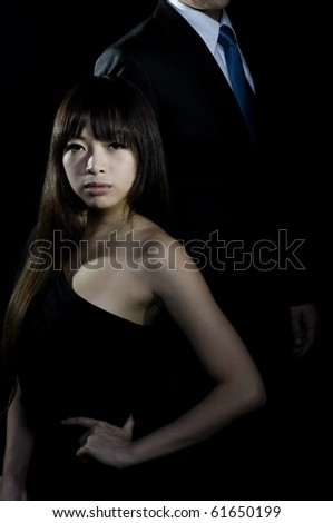 Sophisticated asian woman with man in background - stock photo