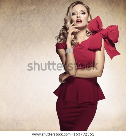 sophisticated elegant lady in red dress with a big bow and jewellery looking in camera with arrogant expression - stock photo