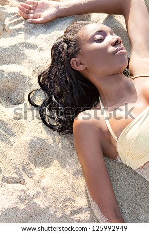 Sophisticated young african american woman laying down on a white sand beach, sunbathing wit her eyes closed, relaxing on holiday. - stock photo