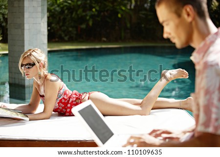 Sophisticated young couple relaxing by the swimming pool of their holiday home garden, and using technology. - stock photo