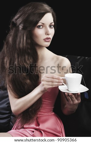 sophisticated young pretty brunette in pink elegant dress sitting on a black sofa and tasting a cup of tea. she looks in to the lens with  three quarters turned faces  and takes a cup of tea - stock photo