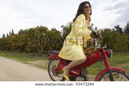 Sophisticated young woman on an old motorbike in an orange grove. - stock photo