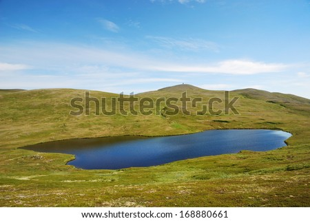 Soroya is a large island in western Finnmark, Norway. The small lake is reflecting the blue sky. It is in the not high mountains sloping. - stock photo