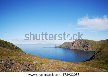 Soroya is a large island in western Finnmark of Norway. There are blue bays, steep capes overgrown with moss. - stock photo