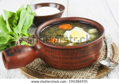 Sorrel soup with eggs in the ceramic pot on the wooden table
