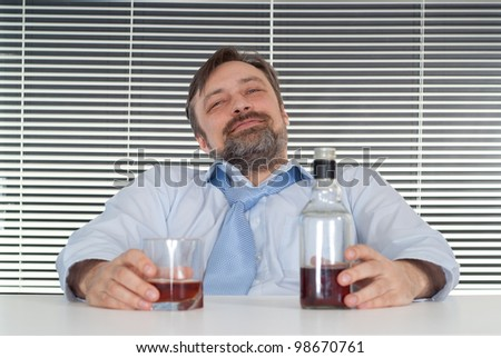 Sorrow business man sitting at a table with a bottle on a light background - stock photo