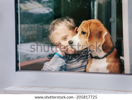 Sorrow little boy with best friend looking through window - stock photo