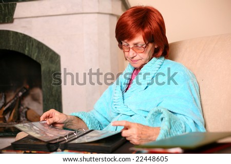 Sorrow senior woman at home holding a group of photos - stock photo