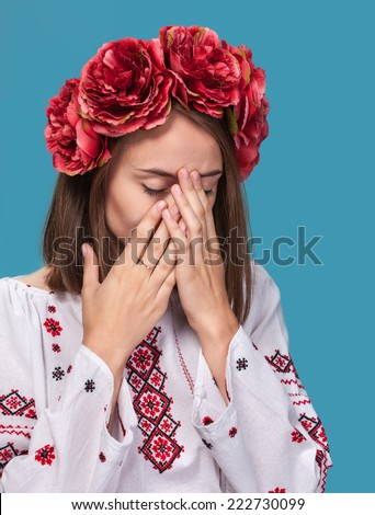 Sorrowful beautiful young girl in Ukrainian national suit  covers her face with her hands - stock photo