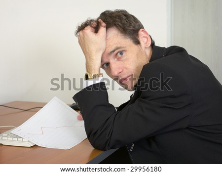 Sorrowful man at the office, on a workplace with graph - stock photo