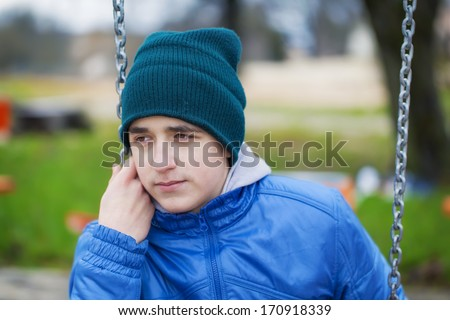 Sorrowful teenage boy swinging in the park - stock photo