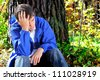 sorrowful teenager sitting in the autumn forest alone - stock photo