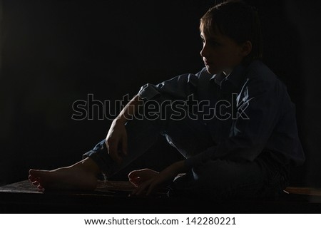 sorrowful young boy on a black background - stock photo