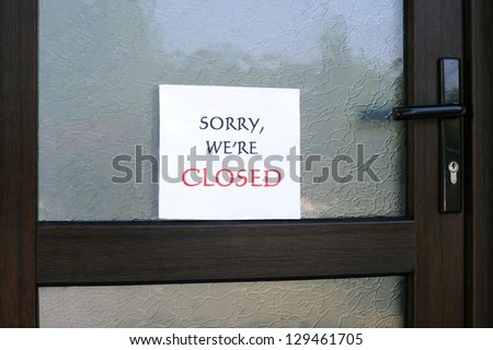 SORRY, WE'RE CLOSED sign on the front door of a little store - stock photo