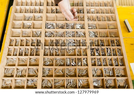Sorting single letters into a box for a vintage printing press - stock photo