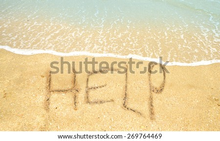sos concept with help written in the sand on the shoreline - stock photo
