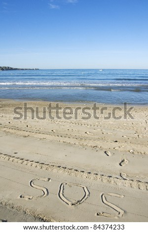 SOS for help written in the sand on the beach - stock photo