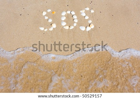SOS in sand on a beach - stock photo