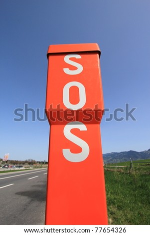 SOS orange sign next to a road by beautiful weather - stock photo