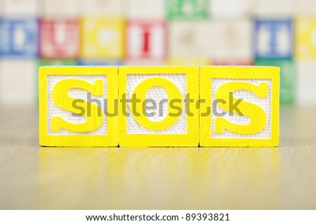 SOS Spelled Out in Alphabet Building Blocks - stock photo