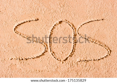 SOS written in the sand on the beach in large letters - stock photo