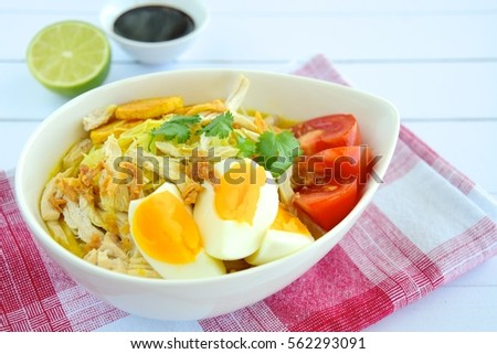 Soto Ayam, Indonesian food, yellow spicy chicken soup with vermicelli, fried potato, hard boiled egg and fried shallot.