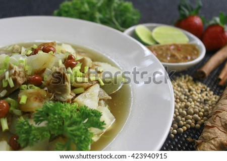 Soto Sabrang. Soto is a traditional Indonesian soup, Composed of broth, meat & vegetables. Soto Sabrang originally from Madura. Sabrang means Singkong in Bahasa, & Cassava in English. Tilt angle. - stock photo