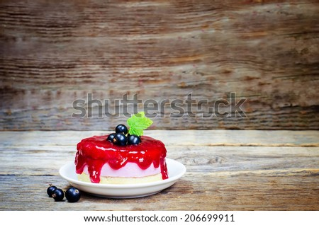 souffle cake with black currant on a dark wood background. toning. selective focus on leave - stock photo