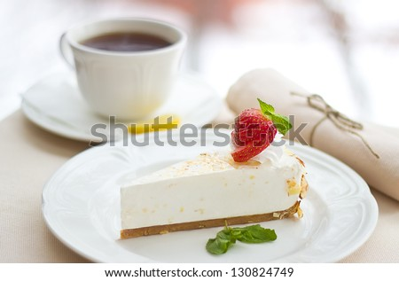 souffle cake with strawberries and a cup of tea on  table - stock photo