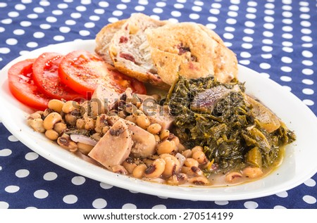 Soul Food Supper of Chunks of Spam in Black-eyed Peas with Collard Greens and sliced tomatoes.  Seasoned with salt pork and chopped red onions.  Blue Polka Dot Country Kitchen Tablecloth. - stock photo