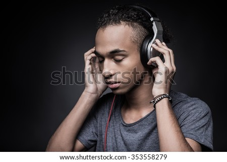 Soul music. Side view of young African man adjusting headphones and keeping eyes closed while standing against black background - stock photo