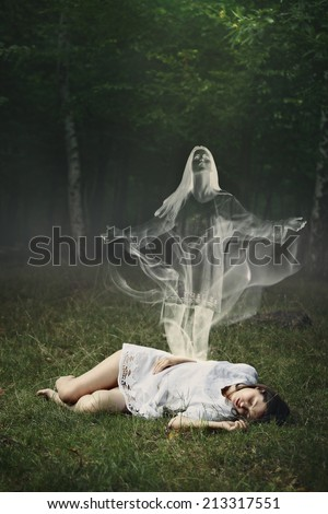 Soul of a sleeping woman leaving her body in a forest  . Surreal and halloween concept - stock photo