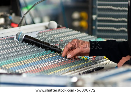 Sound engineer at mixing desk at open air concert - stock photo