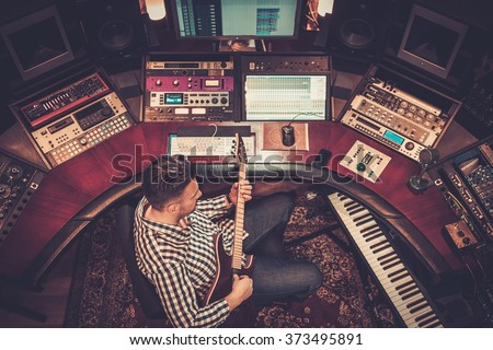 Sound engineer with guitar recording a song in the boutique recording studio. - stock photo