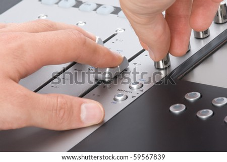 Sound engineer with hands on fader and knob - stock photo